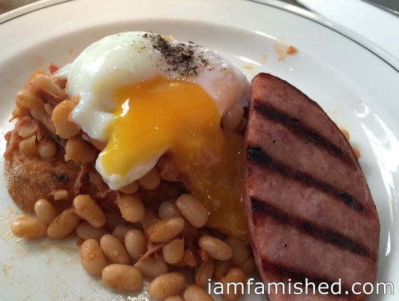 Grilled sausage, smoked hock, braised beans & 65/65 egg (2)